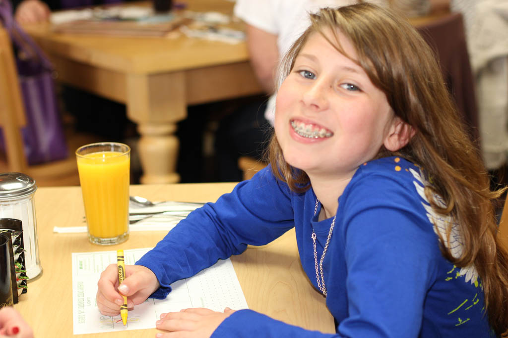 Child Smiling and coloring while eating breakfast